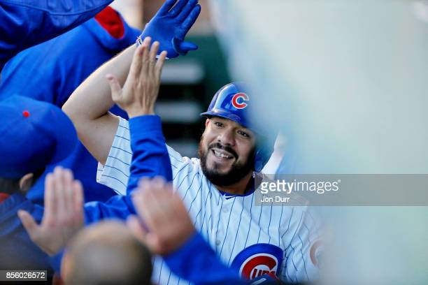 Rene Rivera of the Chicago Cubs is congratulated in the dugout after hitting a home run against the Cincinnati Reds during the seventh inning at...