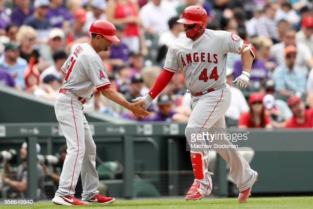 Rene Rivera of the Los Angeles Angels of Anaheim is congratulated by third base coach Dino Ebel after hitting a solo home run in the seventh inning...