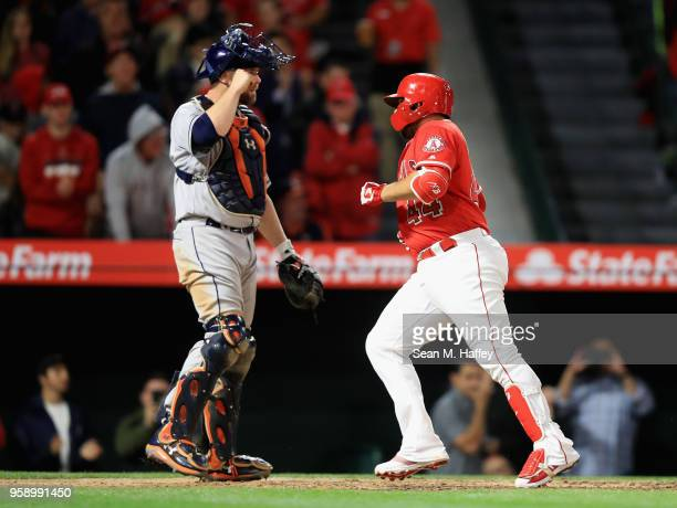 Rene Rivera of the Los Angeles Angels of Anaheim touches home plate after hitting a solo homerun as Brian McCann of the Houston Astros looks on...