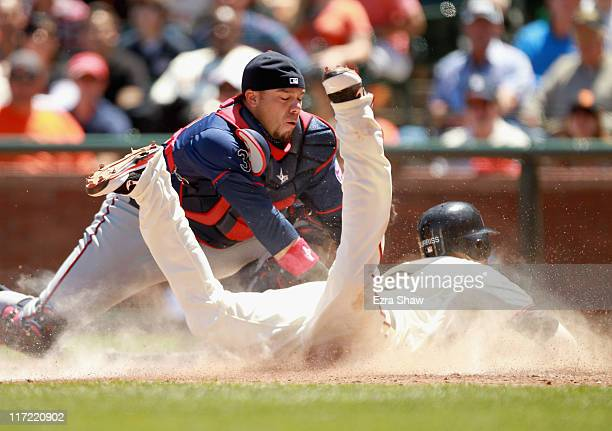 Rene Rivera of the Minnesota Twins tags out Emmanuel Burriss of the San Francisco Giants at home plate in the seventh inning at ATT Park on June 23...