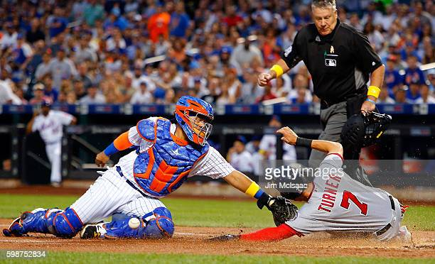 Rene Rivera of the New York Mets can't come up with the ball as Trea Turner of the Washington Nationals scores a run in the first inning on a...