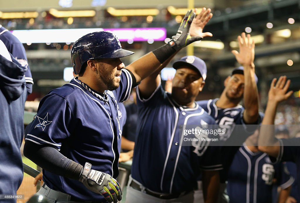 Rene Rivera #44 of the San Diego Padres high-fives teammates in the dugout after hititng a solo home run against the Arizona Diamondbacks during the fifth inning of the MLB game at Chase Field on September 12, 2014 in Phoenix, Arizona.