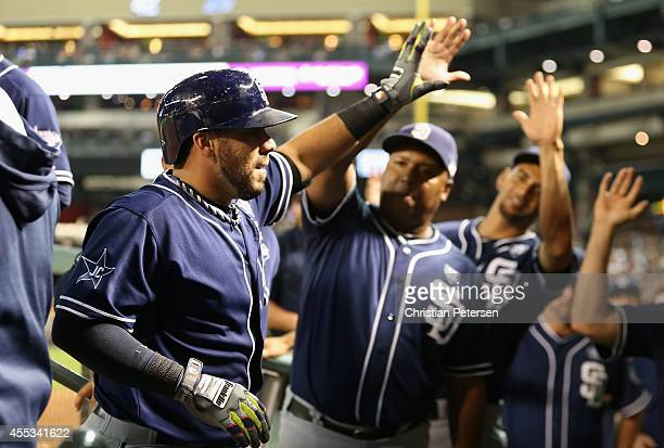 Rene Rivera of the San Diego Padres highfives teammates in the dugout after hititng a solo home run against the Arizona Diamondbacks during the fifth...