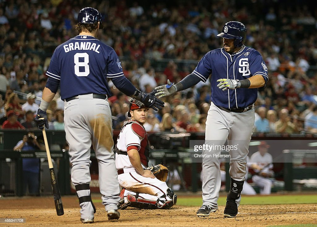 Rene Rivera #44 (R) of the San Diego Padres high-fives Yasmani Grandal #8 after hititng a solo home run against the Arizona Diamondbacks during the fifth inning of the MLB game at Chase Field on September 12, 2014 in Phoenix, Arizona.
