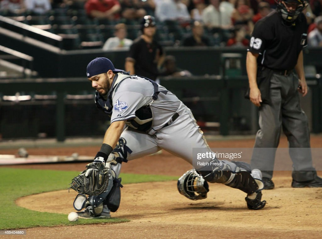 Rene Rivera #44 of the San Diego Padres reaches for a pass ball which advanced Arizona Diamondbacks runners during the seventh inning of a MLB game at Chase Field on September 13, 2014 in Phoenix, Arizona.