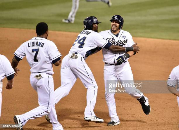 Rene Rivera of the San Diego Padres right is congratulated by Cameron Maybin center and Rymer Liriano after he hit a walkoff single during the tenth...