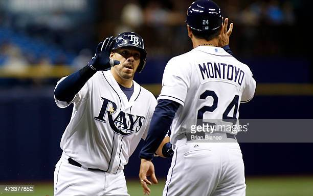 Rene Rivera of the Tampa Bay Rays celebrates with third base coach Charlie Montoyo as he rounds the bases after hitting a threerun home run during...