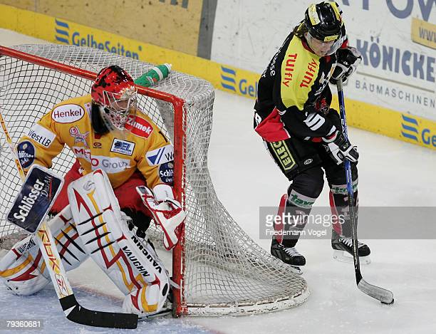 Rene Roethke of Hanover and Jamie Stoor of DEG fight for the puck during the DEL match between Hannover Scorpions and DEG Metro Stars at the TUI...