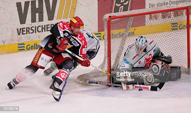 Rene Roethke of Hanover tries to score over Jean Francois Labbe goalkeeper of Nuremberg during the DEL Bundesliga paly off quarter final game between...