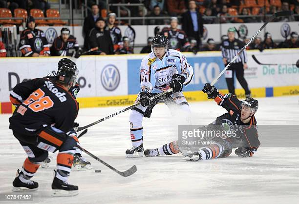 Rene Roethke of Straubing is challenged by Kai Hospelt of Wolfsburg during the DEL match between Grizzly Adams Wolfsburg and Straubing Tigers at the...