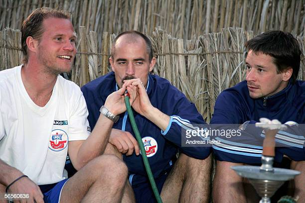 Rene Rydlewicz Magnus Arvidsson and Ronald Maul smoke a water pipe during a desert tour outside of Dubai City during the training camp of German...