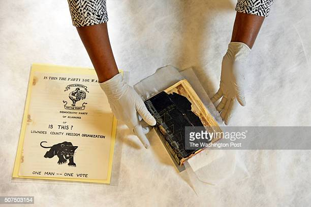 Renee Anderson head of collections handles a Buffalo Soldiers bible from around 1913 and a 1966 pamphlet for the Black Panther Party of Lowndes...