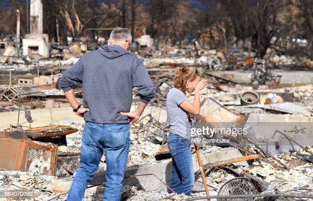 Renee Johnson weeps while sifting through the remains of her burned home in the Coffey Park area of Santa Rosa California on October 20 2017...