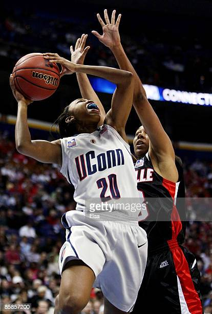 Renee Montgomery of the Connecticut Huskies goes up for two as Monique Reid of the Louisville Cardinals defends during the NCAA Women's Final Four...