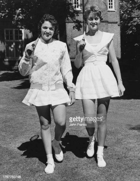 Renee Schuurman and Sandra Reynolds of South Africa pose for a photograph wearing new tennis outfits by fashion designer Teddy Tinling during Lady...
