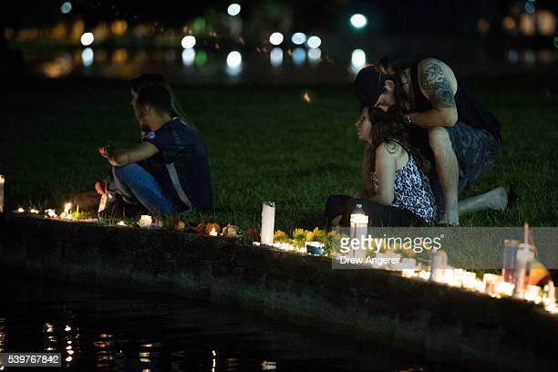 Renee Solita and fiance Doug Comanko share a moment on the edge of Lake Eola where candles were placed for the victims of the nightclub shooting June...