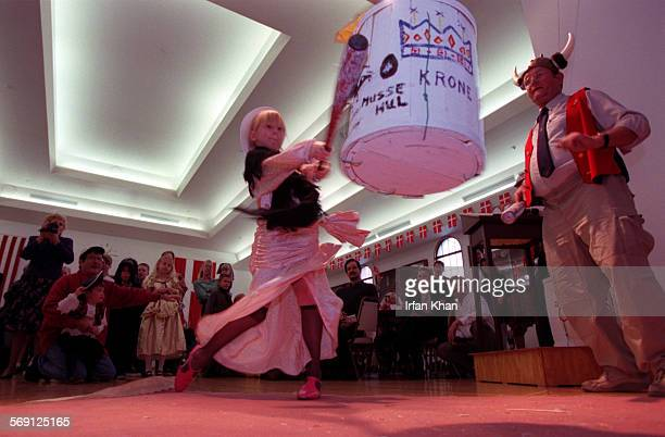Renee Varnas swings a baseball bat at a barrel at a Danish traditional Fastalavn, a lent festival that involves a pinata–like barrel that kids...