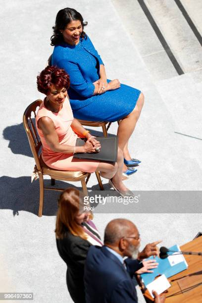 Renel Brooks Moon and Mayorelect London Breed listen to the Rev Amos Brown during the inauguration ceremony of Breed at City Hall July 11 2018 in San...