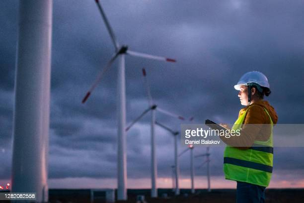 renewable energy systems. electricity maintenance engineer working on the field at a wind turbine power station at dusk with a moody sky behind. blurred motion. - occupation stock pictures, royalty-free photos & images