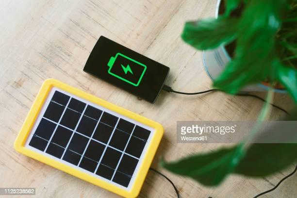 renewable energy technology, solar panel charging a mobile phone battery - fornecimento de energia imagens e fotografias de stock