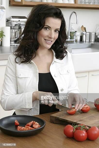 Renewal Of The English Cooking Nigella LAWSON découpant des tomates en quartiers dans la cuisine d'un appartement à LONDRES