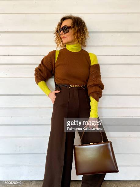 Renia Jaz wearing green roll neck - Joseph brown top with sleeves from Frankie Shop, Bottega Veneta belt, brown trousers from Bouguessa, Celine bag...