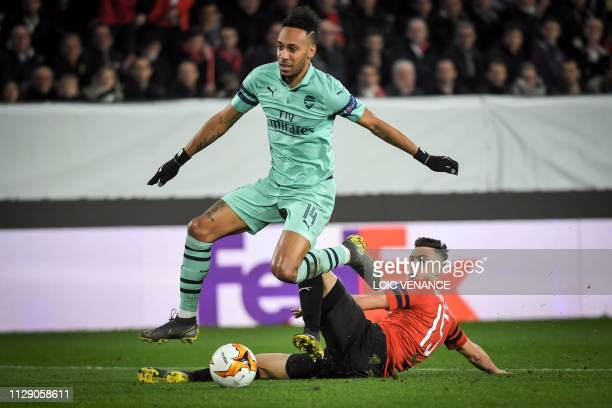 Rennes' Algerian defender Ramy Bensebaini avoids a tackle from Arsenal's Gabonese forward PierreEmerick Aubameyang during the UEFA Europa League...