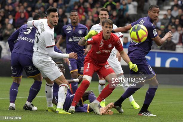 Rennes Algerian defender Ramy Bensebaini vies with Toulouse's Uruguayan goalkepper Mauro Goicoechea and Toulouse's French defender Christopher...