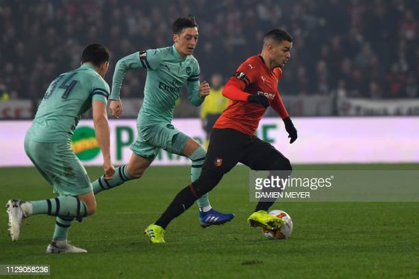 Rennes' French forward Hatem Ben Arfa vies with Arsenal's German midfielder Mesut Ozil during the UEFA Europa League round of 16 first leg football...