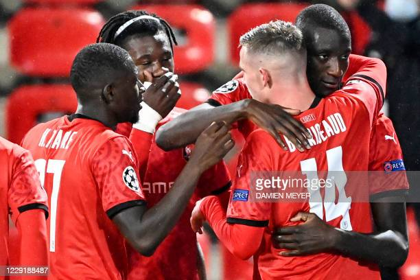Rennes' French forward Sehrou Guirassy is congratulated by teammates Rennes' French midfielder Benjamin Bourigeaud, Rennes' Senegalese forward Mbaye...