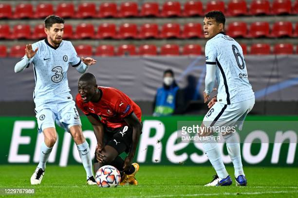 Rennes' French forward Sehrou Guirassy is injured as he fights for the ball with Chelsea's Italian midfielder Jorginho and Chelsea's Brazilian...