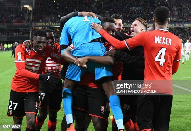 Rennes' French goalkeeper Abdoulaye Diallo is congratulated by his teammates after winning the French League Cup round of 16 football match between...
