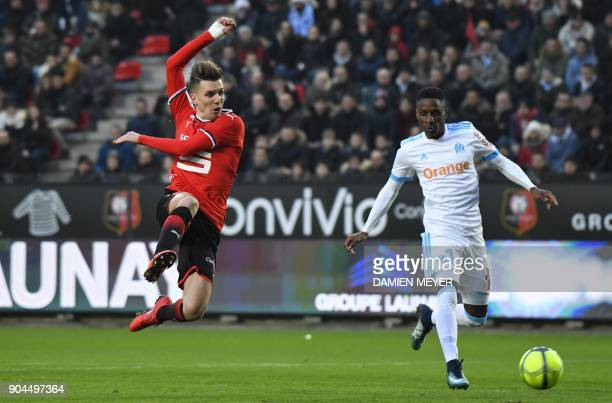 Rennes' French midfielder Adrien Hunou kicks the ball despite Olympique de Marseille's French forward Bouna Sarr during the French L1 football match...