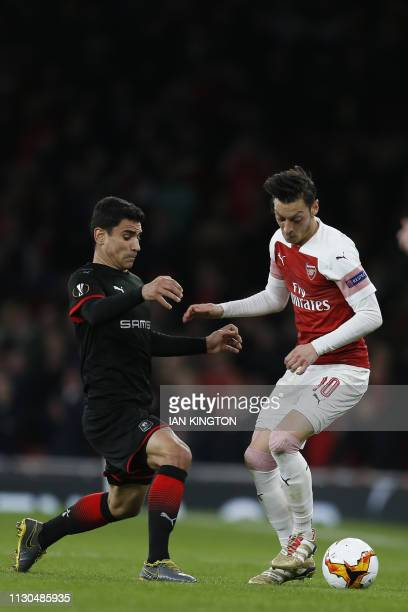 Rennes' French midfielder Benjamin Andre vies with Arsenal's German midfielder Mesut Ozil during the UEFA Europa League Round of 16 second leg...