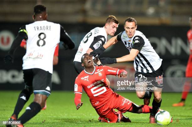 Rennes' French midfielder ChristEmmanuel Faitout Maouassa fights for the ball with Angers' French midfielder Baptiste Santamaria and Angers' French...