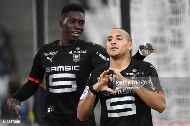 Rennes' midfielder Wahbi Khazri shapes a heart with his hands as he celebrates with a teammate after scoring a goal during the French L1 football...