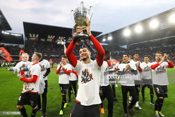 Rennes player Rami Bensebaini celebrates with the French Cup trophy during the Ligue 1 match between Rennes and Monaco on May 1 2019 in Rennes France