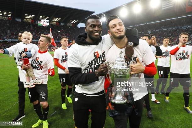 Rennes players Mbaye Niang and Rami Bensebaini celebrate with the French Cup trophy during the Ligue 1 match between Rennes and Monaco on May 1 2019...