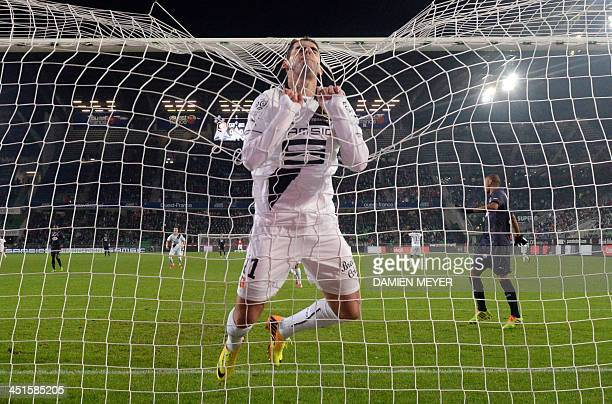 Rennes' Portuguese forward Nelson Oliveira hanging to the goal's net reacts after missing a goal during the French L1 football match Rennes against...