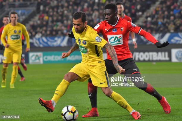 Rennes' Senegalese forward Ismaila Sarr vies with Paris SaintGermain's Brazilian defender Daniel Alves during the French cup football match Rennes vs...