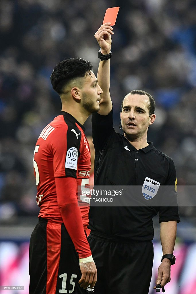 Rennes'Algeria defender Ramy Bensebaini (L) receives a red card from French referee Benoit Millot (R) during the French L1 football match Olympique Lyonnais (OL) vs Rennes (Stade Rennais) on December 11, 2016, at the Parc Olympique Lyonnais stadium in Decines-Charpieu, central-eastern France. / AFP / JEFF