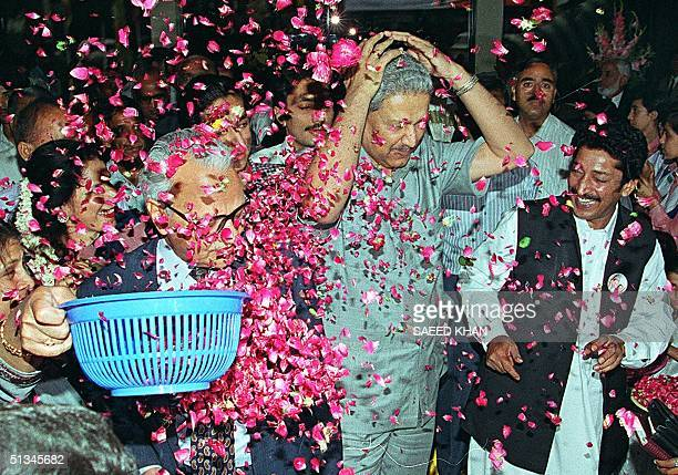 Renowned Pakistani scientist Abdul Qadeer Khan tries to shield his face as a woman throws fresh rose pedals over him during a reception ceremony for...