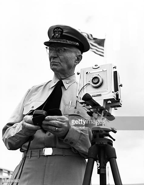 Renowned photographer Edward Steichen takes photographs at the USS Arizona Memorial in Pearl Harbor Hawaii at its dedication in 1962 He wears the...