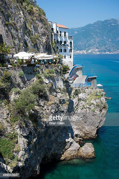Renowned seafood restaurant Da Zaccaria clings to the side of a cliff above the sea in Amalfi, Italy. Taken on Italy's Amalfi Coast.