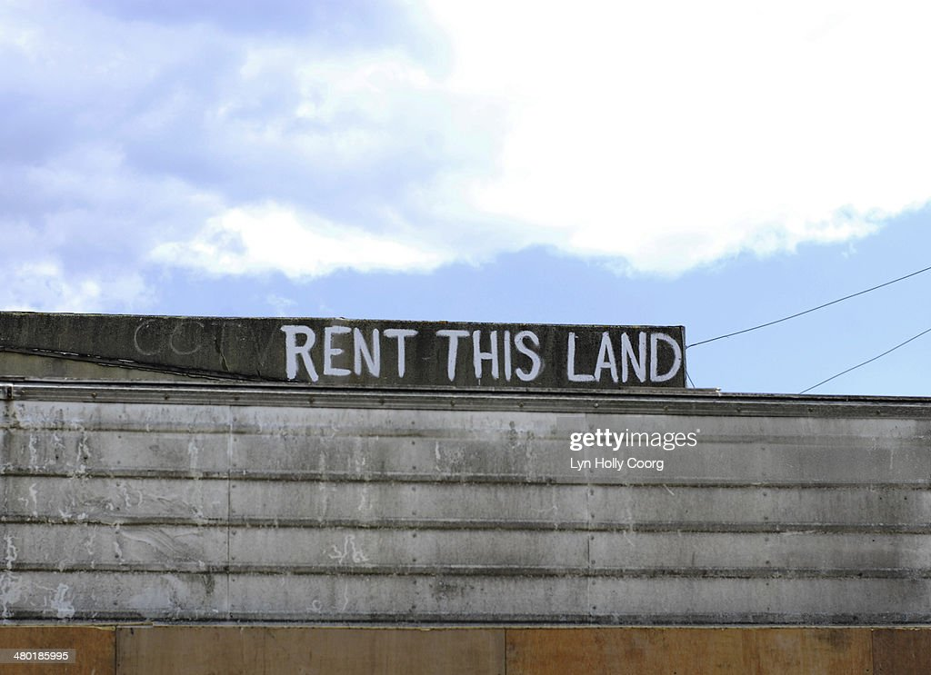 'Rent This Land' sign against blue sky : Stock Photo