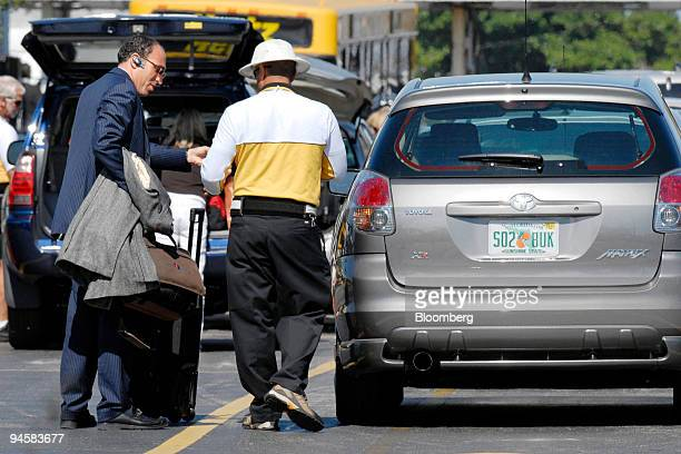 A rental car customer talks with a Hertz agent after returning his Toyota Matrix to the Hertz Car Rental center at Palm Beach International Airport...