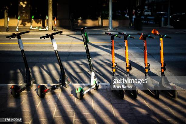 rental scooters on sidewalk - electric scooter stock pictures, royalty-free photos & images