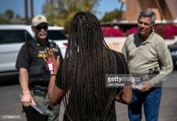 Renter speaks with Maricopa County constables serving an eviction order on October 2, 2020 in Phoenix, Arizona. Thousands of court-ordered evictions...