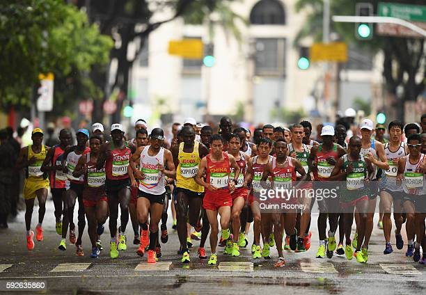 Renxue Zhu of China and Alemu Bekele of Bahrain lead the pack during the Men's Marathon on Day 16 of the Rio 2016 Olympic Games at Sambodromo on...
