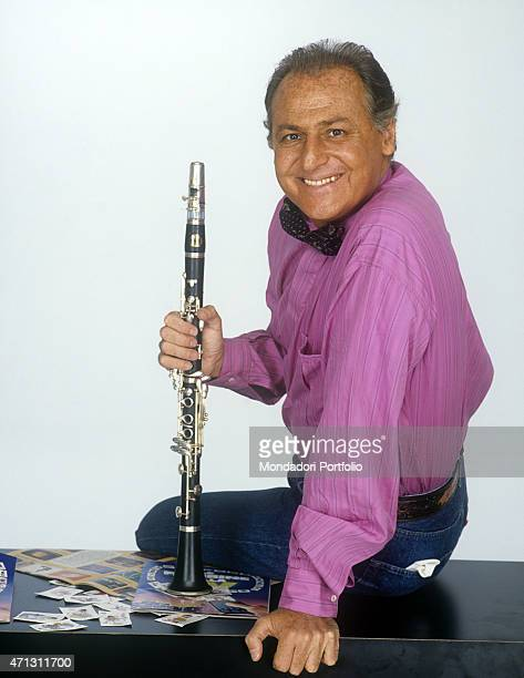 Renzo Arbore television presenter ad jazzman famous all over the world sits on a writing desk holding his inseparable clarinet Italy 1988